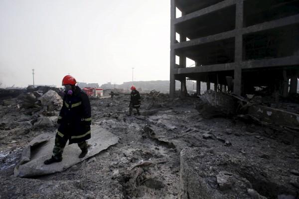 天津大爆炸過後,消防人員戴著全罩式口罩,挺進爆炸區域進行搜救工作。(路透)