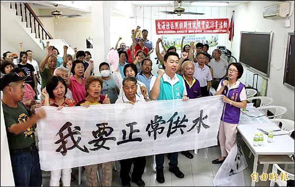 台中東海里常缺水,市議員陳世凱(右二)、東海里長陳玉華(右一)昨天帶領民眾拉白布條要求正常供水。(記者陳建志攝)
