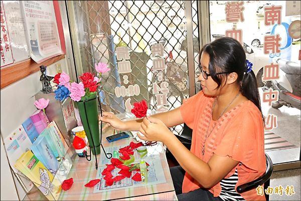 藝術家陳昭靜製作紙玫瑰,送捐血民眾。(記者詹士弘攝)