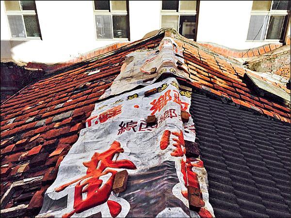 歷史建築元昌行,屋頂中脊屋瓦全掀了起來,只能緊急蓋上帆布。(李奕興提供)