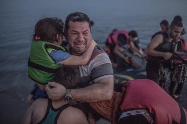 一名敘利亞難民平安上岸後,激動地抱住兒女哭泣。(圖擷自《紐約時報》)