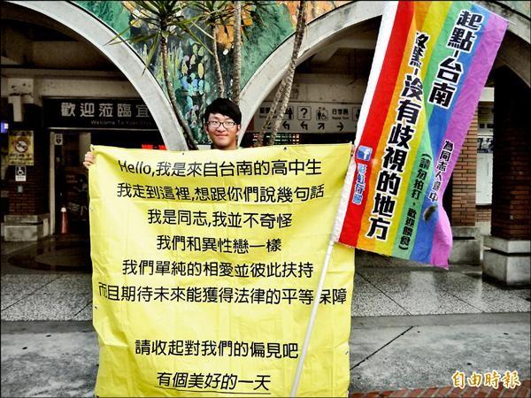 張澤瑜昨天情人節下午在宜蘭火車站舉海報,呼籲收起偏見。(記者簡惠茹攝)