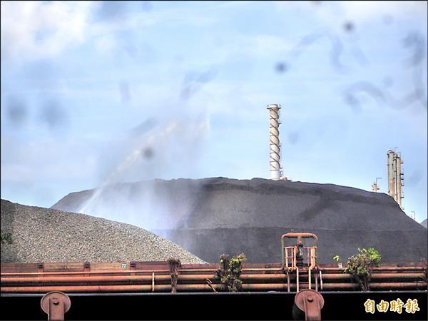 中鋼原料堆置場設置防風阻隔牆,並進行堆料灑水避免逸散。(記者黃旭磊攝)