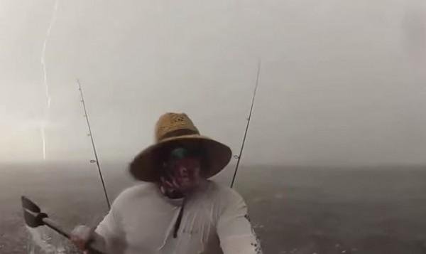 美國一名男子乘獨木舟到水上,不料竟遇暴風雨,他連忙划回岸上。畫面中可見他被後的雲層和閃電。(圖擷取自YouTube)
