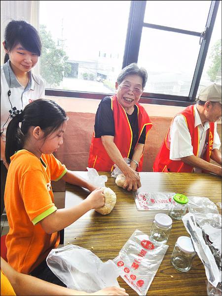 參加祖父母節活動的獨居長者,與小朋友一起作味噌,十分開心。(華山創世基金會豐原站提供)