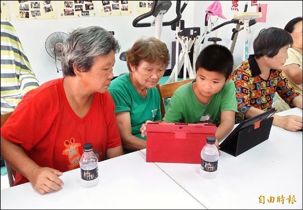 孫子輩小助教林庭偉(左三),協助教導阿公阿嬤學平板電腦,以後不再LKK。(記者楊金城攝)