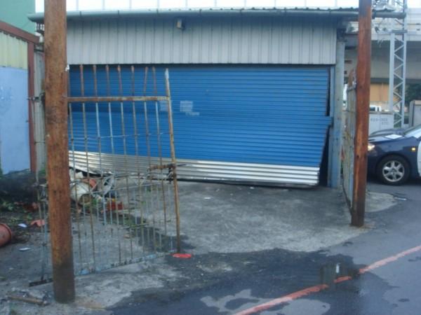 休旅車撞進藍色鐵捲門後,捲門又關了起來,完全不知有車撞入(記者葉永騫翻攝)