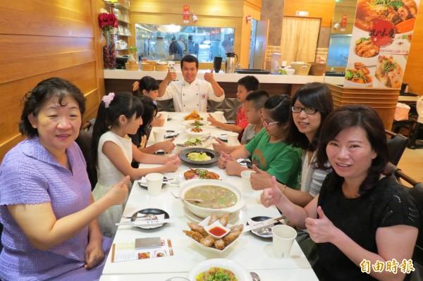 「況味慶」老闆邱欣慶(中)免費招待沐風的孩子用餐(記者蘇金鳳攝)