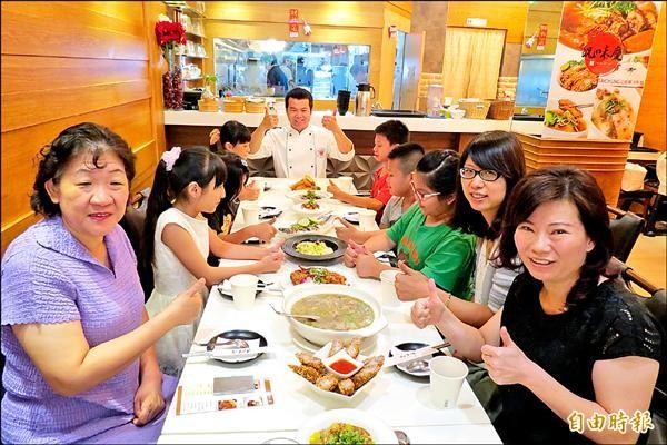 「況味慶」老闆邱欣慶(中)免費招待沐風關懷協會的孩子用餐。(記者蘇金鳳攝)