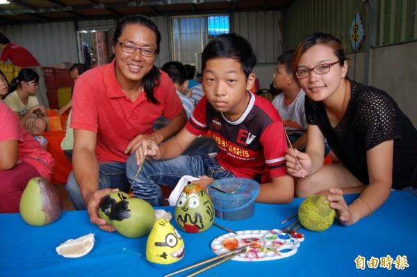 李佳翰(右三)、高心儀(右一)夫婦教導家扶兒在文旦上彩繪。(記者楊金城攝)