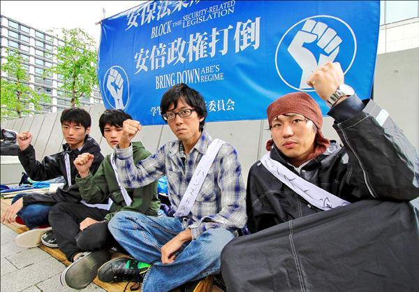 四名日本男大學生二十七日起在國會大廈前絕食抗議,希望阻止參議院通過允許日本自衛隊為協防盟國而出兵的新安保法。(法新社)
