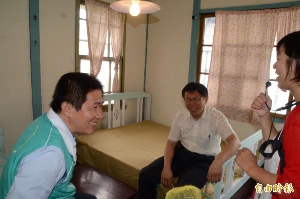 柯P到溪州鄉「成功旅社」參觀,好奇的坐在老床舖上,導覽員說「開房間」,柯p跟立委參選人陳文彬笑開懷。(記者顏宏駿攝)