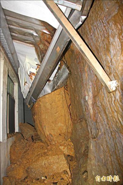 基隆市崇德路山壁坍方,落石砸進汽車材料行倉庫。(記者林欣漢攝)