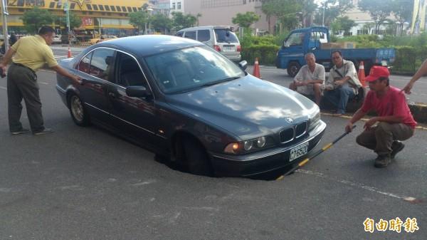 今日下午台南市安平區的柏油路突然塌陷,有民眾戲稱柏油路想「吞下」BMW。(記者王捷攝)