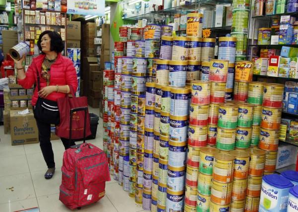 中國人在全球各地瘋狂搶購嬰兒奶粉。圖為中國婦女在香港商店詢問奶粉價格。(路透)