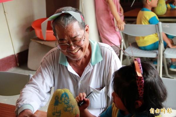 幼兒園學童與吳阿公一起彩繪文旦柚,阿公笑開懷。(記者王秀亭攝)