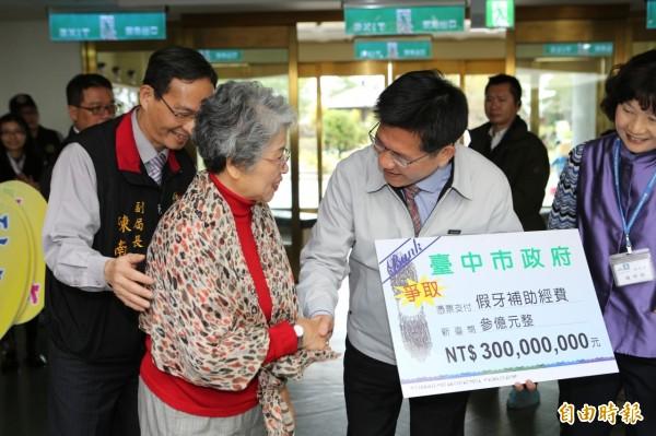 市長林佳龍(舉牌者)探視養護中心銀髮族,承諾老人假牙補助經費提高到3億元,結果供不應求,將加碼至5.5億元。(記者黃鐘山攝)