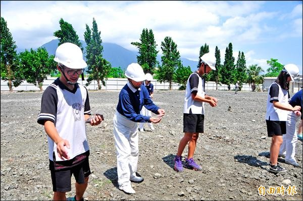 國風國中九年級學生、慈濟志工,將油菜花種子撒在新校舍預定地。(記者花孟璟攝)