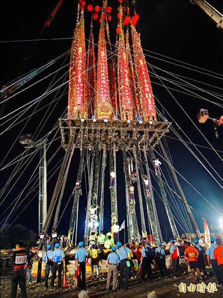宜蘭頭城搶孤昨晚11點多開賽,選手以疊羅漢方式,抓著塗有牛油的孤柱往上攀爬。(記者江志雄攝)