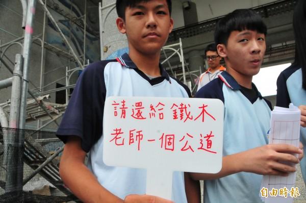 學生今天在校園舉牌聲援老師。(記者花孟璟攝)