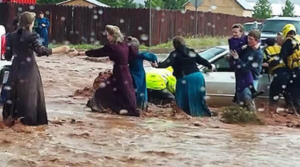 美國一小鎮突然暴雨,造成當地淹水,民眾冒險涉水。(圖擷取自NBC)