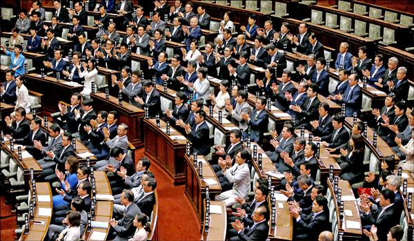 日本參議院十九日凌晨過後以一四八對九十票,投票通過新安保法案後,執政黨自民黨參議員紛紛起立鼓掌。(路透)