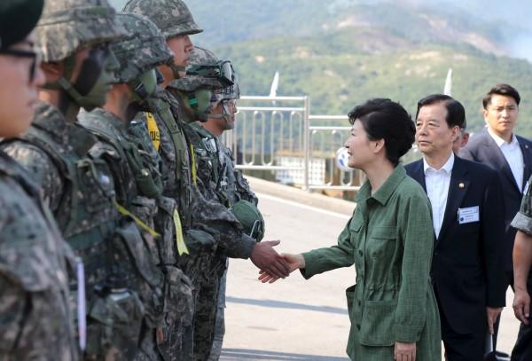 南韓總統朴槿惠今頒發「特別休假證」給南韓軍隊中副士官及以下的官兵。圖為上個月美韓聯合軍演,朴槿惠和軍人握手資料照。(路透)