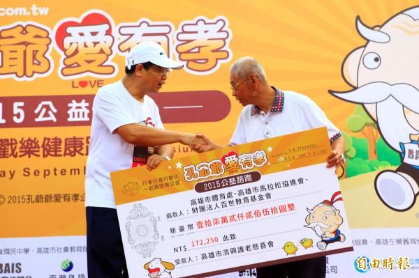 高雄市馬拉松協進會理事長蔡清華(左)代表主辦單位捐款給高雄市濟興護老慈善會等公益團體。(記者洪定宏攝)