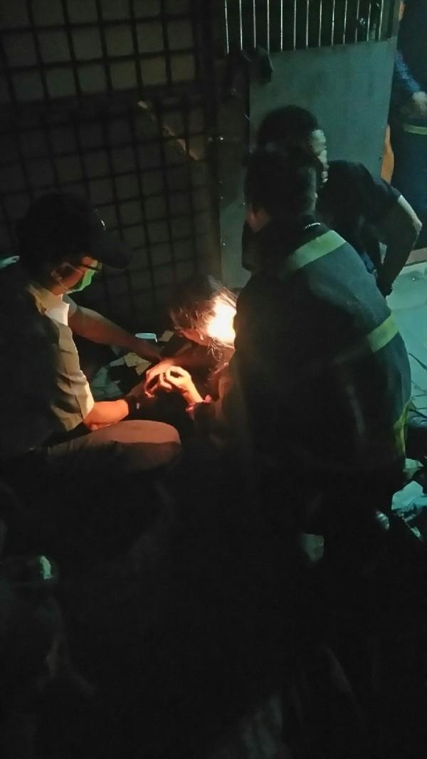 陳姓女子被拉上頂樓(左2),消防人員替她檢傷。(記者吳仁捷翻攝)