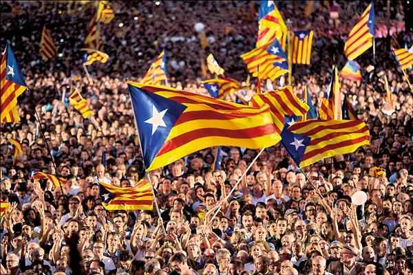 西班牙自治區加泰隆尼亞廿七日舉行形同獨立公投的議會大選,獨立派可望取得過半數席次。圖為獨立派支持者廿五日在巴塞隆納的造勢活動上揮舞加泰隆尼亞旗幟。(美聯社)