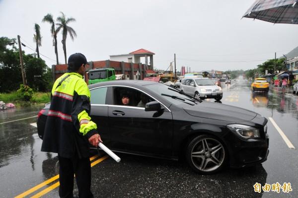 警:「前面封路不能走了,趕快迴轉」!遊客拉下車窗詢問,表情一臉失望。(記者花孟璟攝)