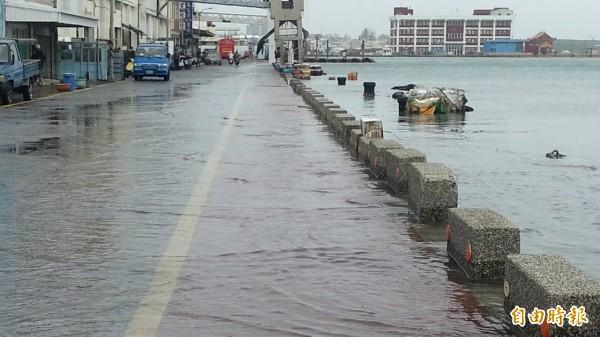 杜鵑颱風來襲,適逢大潮導致水漫道路奇景。(記者劉禹慶攝)