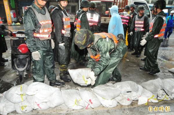 花蓮中午過後雨勢增強,國軍官兵出動30員到吉安鄉海岸路協助堆沙包。(記者花孟璟攝)