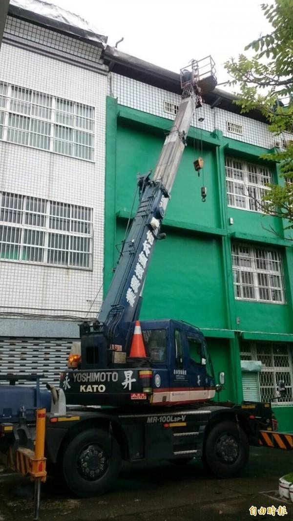校方派吊車,由人員把掀翻的屋頂固定住。(記者顏宏駿攝)