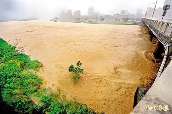 強颱杜鵑挾帶風雨而來,新店溪上游的滾滾泥水傾洩而下,讓溪水水面不斷上漲。(記者叢昌瑾攝)