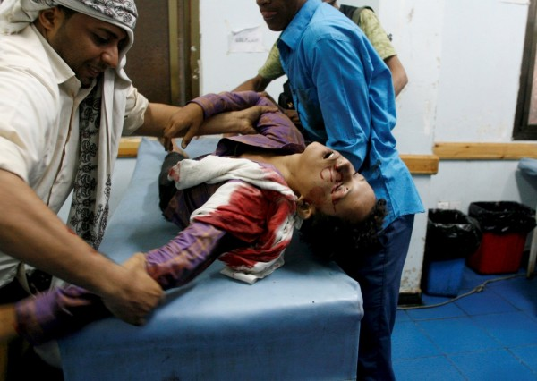 志工幫助一個在反政府軍與政府軍爭戰中受傷的婦女。(路透)