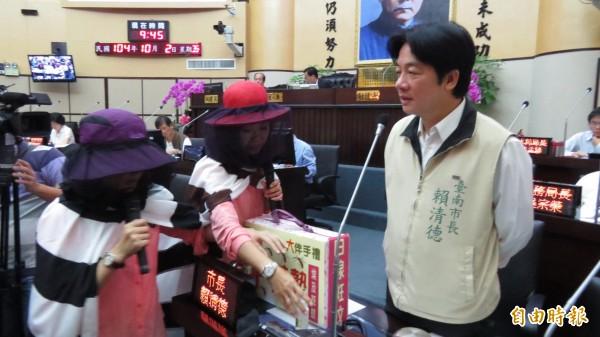 林燕祝(左)、林美燕(中)送賴清德(右)登革熱伴手禮嘲諷。(記者蔡文居攝)