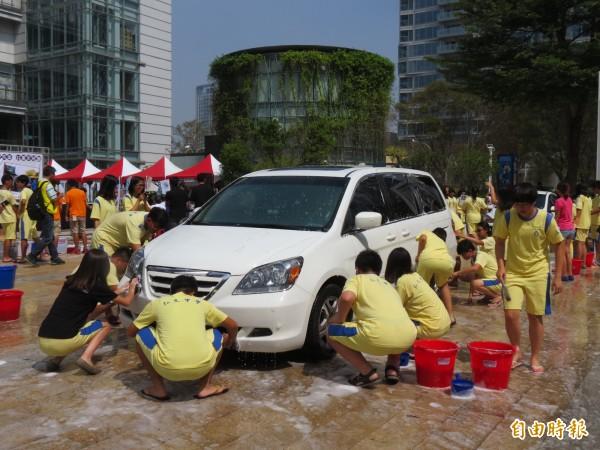 弘文中學200餘學生上街「開派對」,響應公益洗車助聽損兒。(記者蘇孟娟攝)