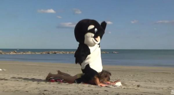 鯨鯊人偶模仿訓獸師騎在鯨鯊背上,跑去壓在比基尼女郎背上。(圖擷自YouTube)