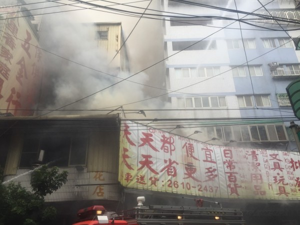 八里華峰一街一棟公寓3樓竄出大量濃煙。(記者黃捷翻攝)