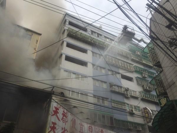 消防人員架雲梯從上方射水灌救。(記者黃捷翻攝)