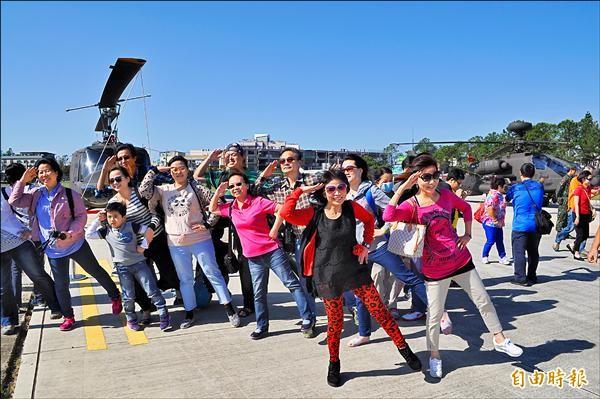 民眾在阿帕契攻擊直升機前,擺出抬腿行舉手禮的姿勢拍照留念。(記者周敏鴻攝)