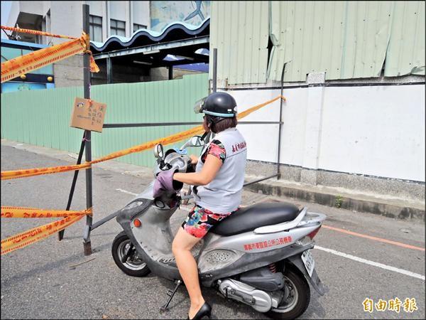 黃純美昨騎車示意,表示受傷的邱姓老翁晚間看不清楚、又不知道路已封閉,因此撞上鐵杆受傷。(記者王善嬿攝)