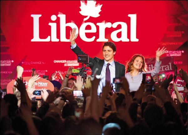 杜魯道(左)確定獲勝後,在蒙特婁發表勝選演說,也不忘在台上和妻子曬恩愛。(彭博)