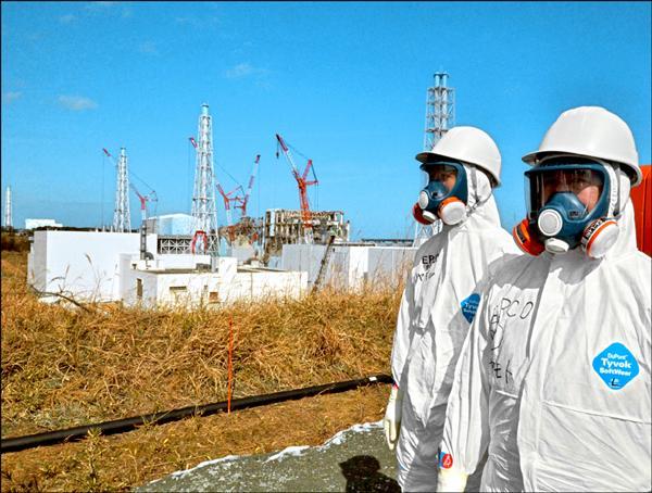 日本厚生勞動省首次認定一名曾在福島核一廠工作的男性罹癌員工,符合職災申請。圖為東京電力公司工作人員站在福島核一廠前。(法新社檔案照)