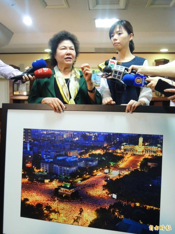 高雄市長陳菊向洪慈庸展示兩年前「凱道萬人送仲丘」的空拍圖,表示這張圖讓她很感動,她時時藉由這張圖片,提醒自己「不要忘記人民的力量。」(記者葛祐豪攝)