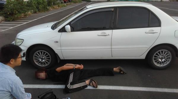 鍾嫌在贓車旁被壓制在地逮捕。(記者許國楨翻攝)