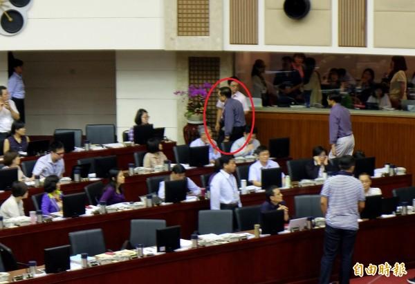 研考會主委陳銘薰(紅圈處)在議場上喊要辭職,隨即收拾包包離去,秘書長蘇麗瓊等人上前勸說,但陳不理會,直接離開。(記者盧姮倩攝)