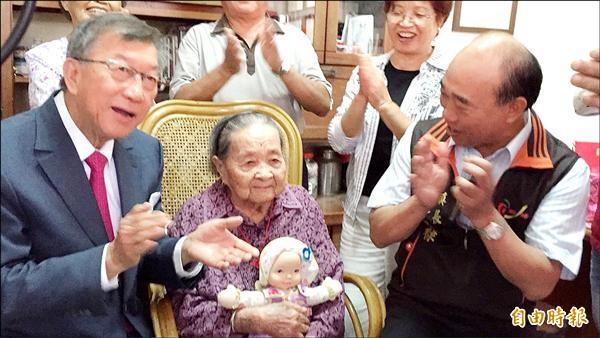 愛玩洋娃娃的102歲人瑞彭榮妹(中),還很擅長唸吉祥的客家四句詩,讓縣長邱鏡淳(左)、新埔鎮長林保祿(右)忍不住鼓掌叫好。(記者黃美珠攝)