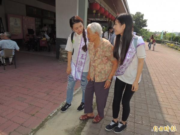 初選出的毛豆公主們,溫柔、耐心地牽著長輩前往參觀有機蔬菜園。(記者林孟婷攝)